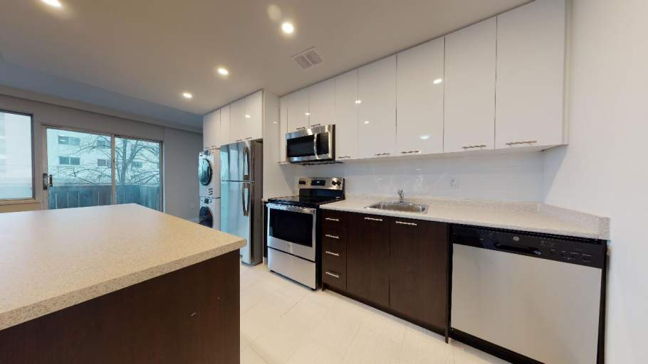 Renovated kitchen with stainless steel appliances, island counter, and in-unit laundry