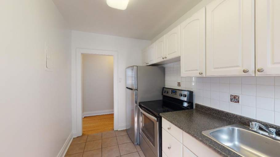 Renovated kitchen with stainless steel appliances and white cabinets