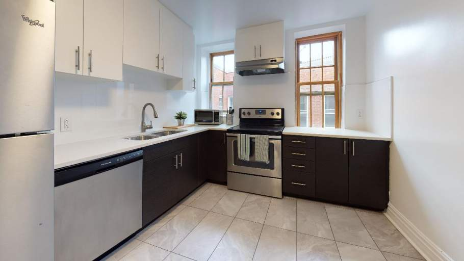 Renovated kitchen with stainless steel appliances, dark-brown cabinets, and white counters