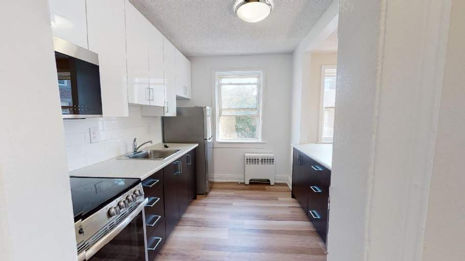 Renovated kitchen with laminate flooring, stainless steel appliances, and dark brown cabinets