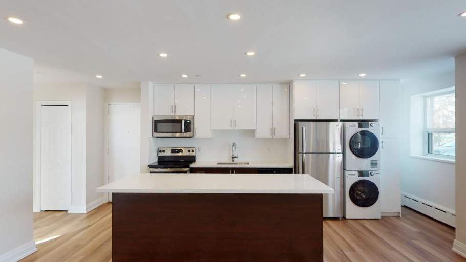 Renovated kitchen with stainless steel appliances, white and dark brown cabinets, and in-suite laundry