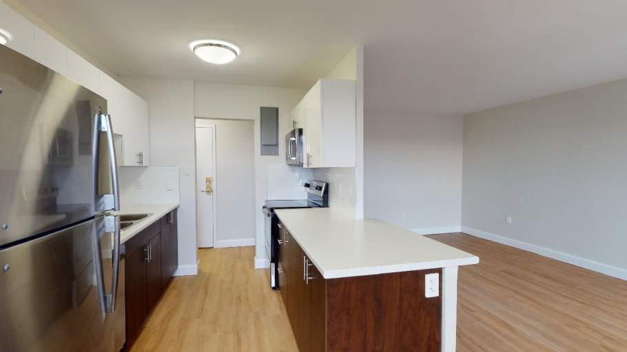 Renovated kitchen with stainless steel appliances, and dark brown and white cabinets