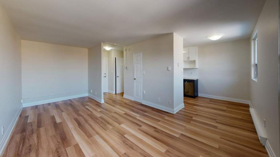 Bright and spacious living room with laminate flooring and attached kitchen