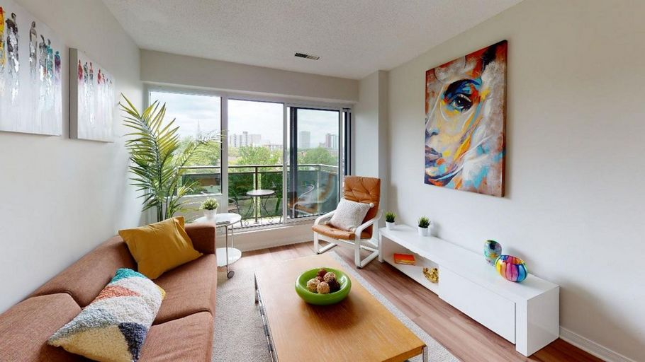 Bright and spacious living room with laminate flooring, seating area, and sliding door to the balcony