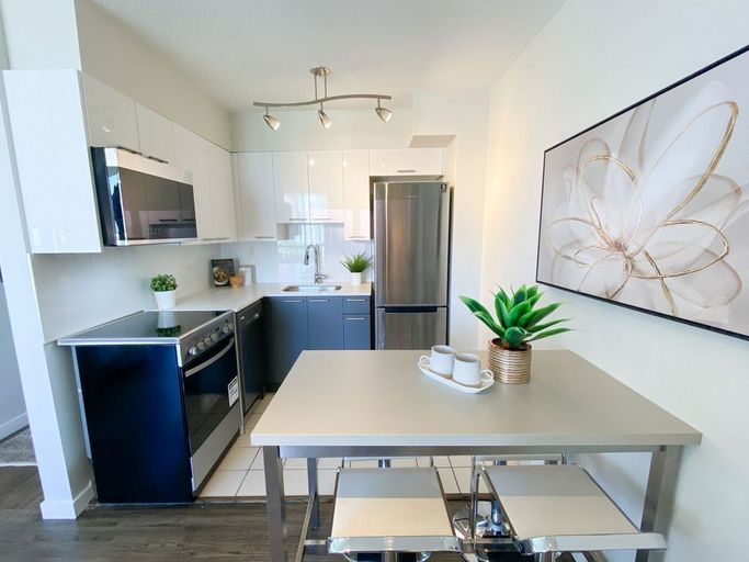 Renovated kitchen with stainless steel appliances, dining table, and dark grey and white cabinets
